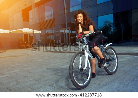 happy brunette sports woman with curly hair in tight clothes on a bicycle outdoors - stock photo
