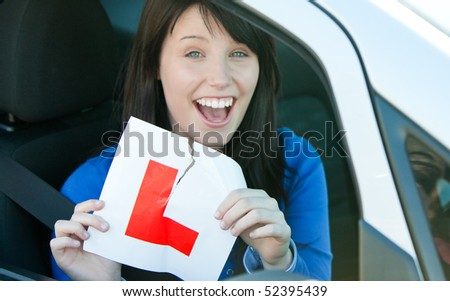 Happy brunette teen girl sitting in her car tearing a L-sign after having her driver's licence - stock photo