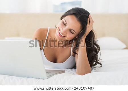 Happy brunette using her laptop at home in bedroom