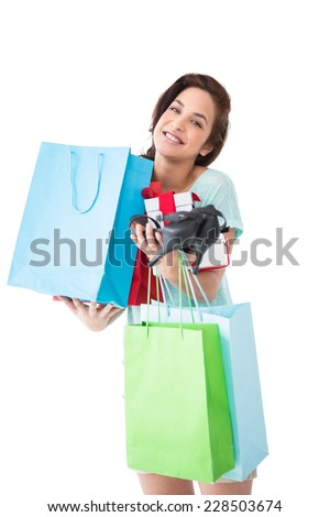 Happy brunette with shopping bags and gifts on white background