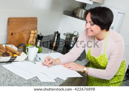 Happy brunette woman applying for bank loan at kitchen - stock photo