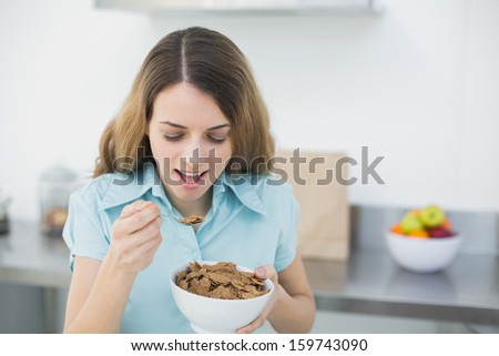 Happy brunette woman eating cereals standing in her kitchen at home - stock photo