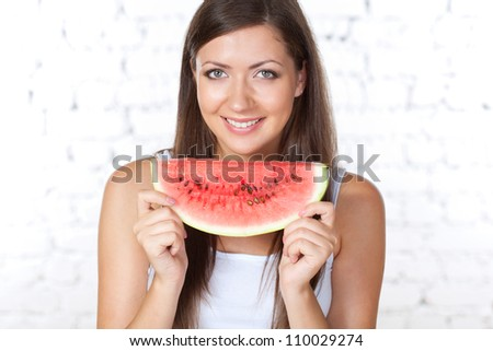 happy brunette woman holding watermelon over white