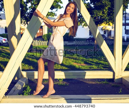 Happy brunette woman in a dress relaxing fun in the park leaning on wooden piles in the park enjoy your vacation, fashion style urban life. Smiling girl bright summer day. Cheerful clowns joking. - stock photo