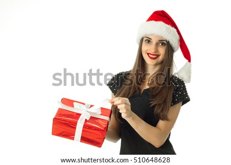 happy brunette woman in santa hat smiling with red gift in hands isolated on white background