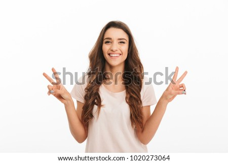 Happy brunette woman in t-shirt showing peace gestures and looking at the camera over white background