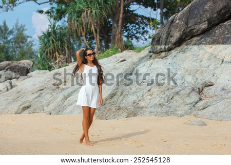 happy brunette woman in white sun dress walking along the beach - stock photo