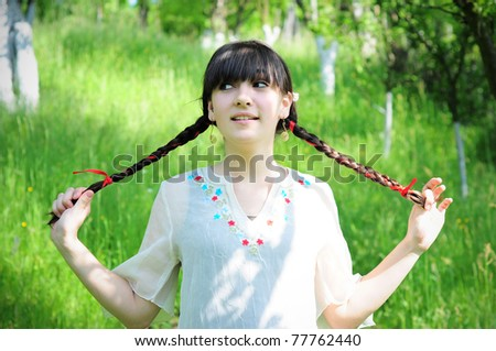 Happy brunette young girl in nature - stock photo
