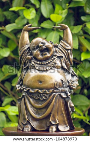 happy buddha statue with green leafs as background - stock photo