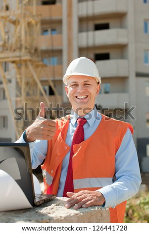 Happy builder in hardhat works on the building site