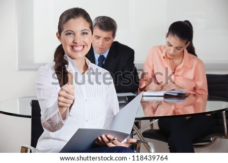 Happy busines woman with files in office holding her thumbs up - stock photo
