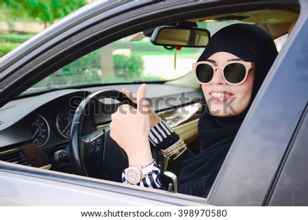 Happy business arabic lady in dark abaya and hijab driving her car and showing thumb up. Smiling arabian lady in sunglasses taking steering wheel of her new car. - stock photo