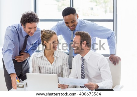 Happy business colleagues reviewing a report at desk in office - stock photo