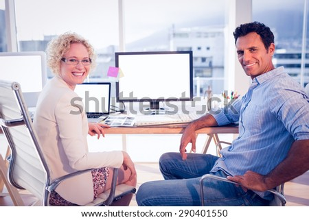 Happy business colleagues smiling at the camera in the office - stock photo