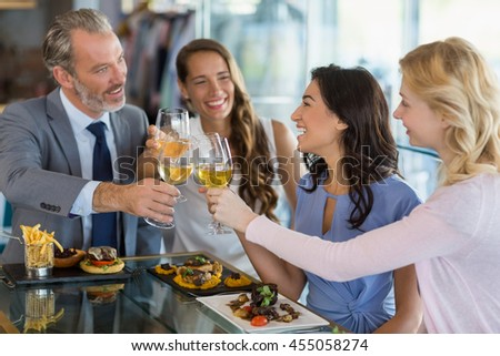 Happy business colleagues toasting beer glasses while having lunch in a restaurant - stock photo