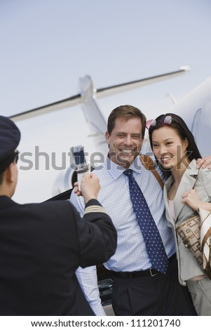 Happy business couple giving pose while airplane captain clicking photo at airfield - stock photo