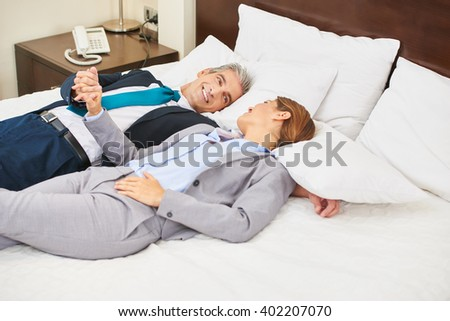 Happy business couple laying on bed in a hotel room and holding hands - stock photo