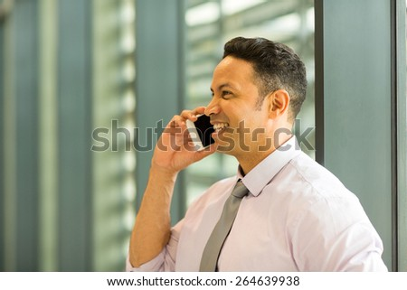 happy business executive talking on mobile phone in office - stock photo