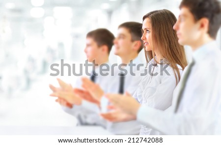 Happy business group applauding at the office - stock photo