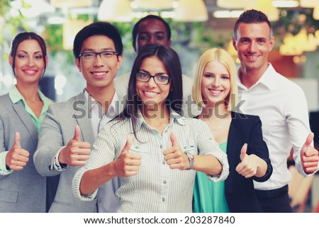 Happy business group giving thumbs up - stock photo