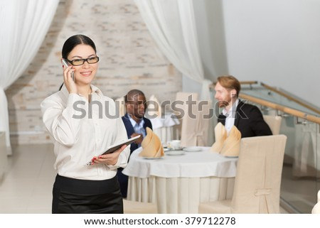 Happy business lady holding tablet PC and speaking over mobile phone in restaurant during business meeting.