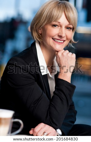Happy business lady posing in restaurant, hand on chin - stock photo