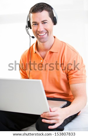 Happy business male on laptop with headset on smiling.