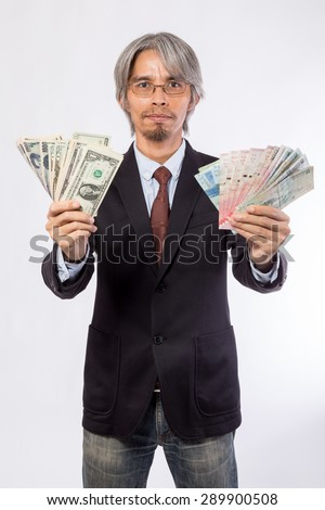 Happy business man hold China , hongkong , united state of america, korea and japan money over a white background, asian model 30s - 40s - stock photo