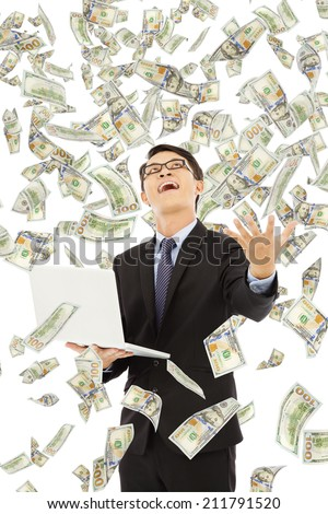 happy business man holding a laptop with money rain