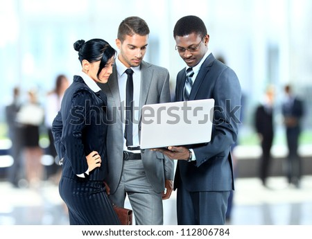 Happy business man holding a modern laptop computer with his team - stock photo