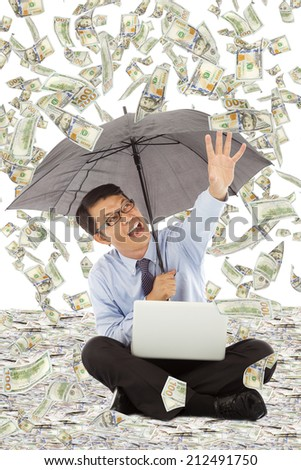happy business man holding a umbrella and catching money - stock photo