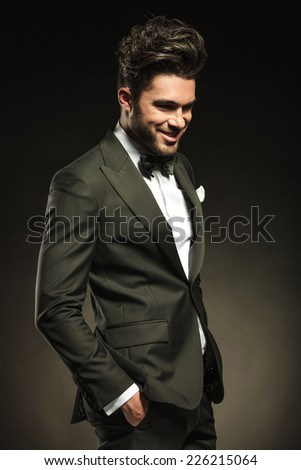 Happy business man holding both hands in pocket while smilling and looking down.