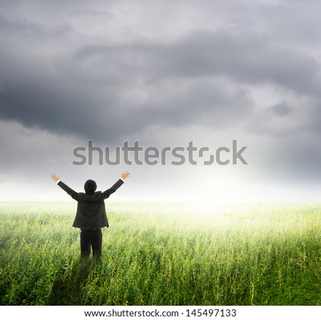 Happy business man in green fields and rainclouds