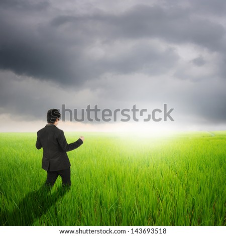 Happy business man in green rice field and rainclouds - stock photo
