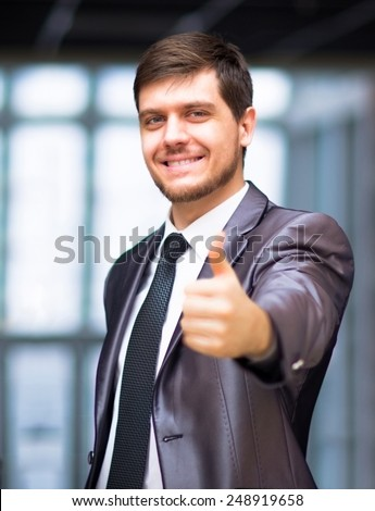 Happy business man in urban city holding thumbs up - stock photo