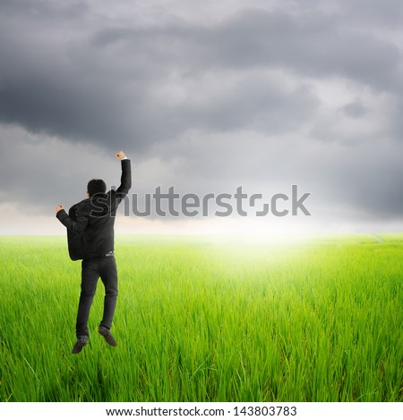 Happy business man jumping in green rice field and rainclouds