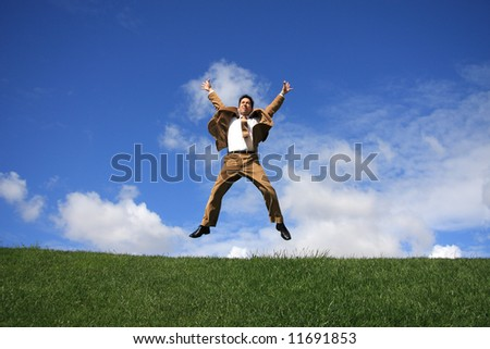 Happy business man jumping on a meadow