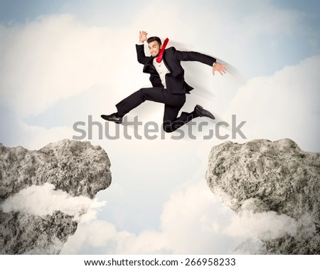 Happy business man jumping over a cliff concept