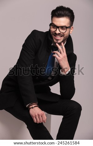 Happy business man laughing while sitting on a chair, holding two fingers to his chin. - stock photo