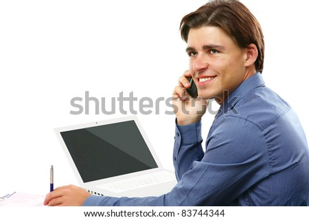 Happy business man on cell phone in front of laptop isolated on white background - stock photo