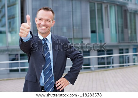 Happy business man outside holding his thumbs up - stock photo