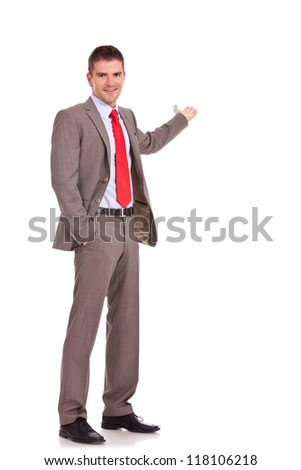 Happy business man presenting something in his back, with a hand in his pocket. isolated on white background - stock photo