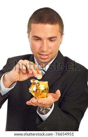 Happy business man putting coin in a gold piggy bank isolated on white background