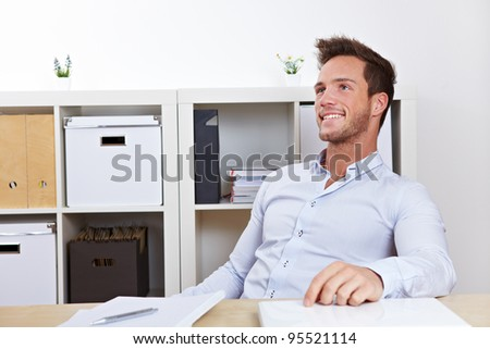 Happy business man relaxing in office at desk leaning back - stock photo