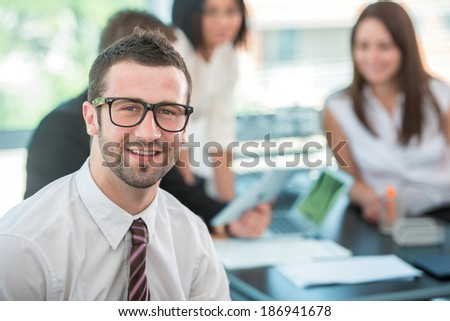 Happy business man sitting in modern office - stock photo