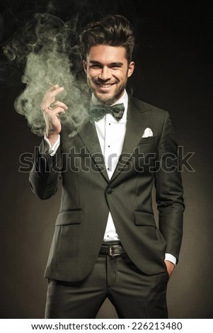 Happy business man smiling for the camera while holding a smoking cigarette in his right hand. - stock photo