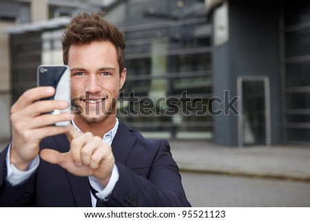 Happy business man taking pictures with smartphone in city