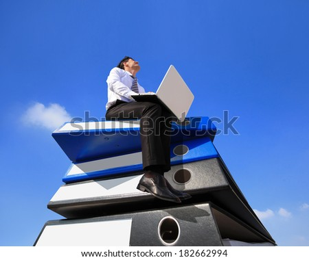 Happy business man using notebook computer and sitting on lots piles of document folders, technology concept - stock photo