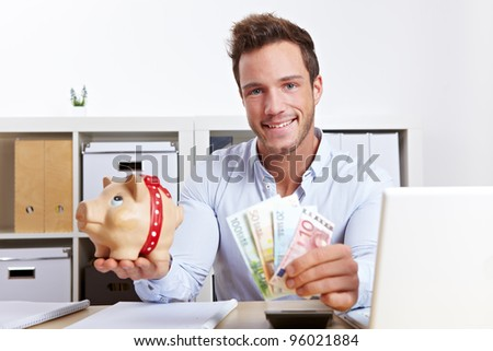 Happy business man with piggy bank and money in office - stock photo
