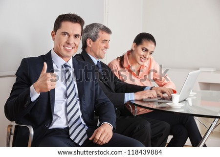 Happy business manager holding his thumbs up with team in the background - stock photo